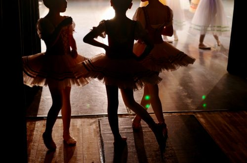 stepping out dark shadow images of three young girls in dancing tutu's backstage waiting to dance