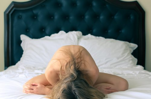 humiliation white woman sitting with legs crossed on a bed with white sheets and black head board with blond hair and arms tucked under her chest