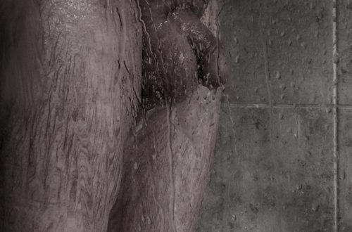 white male in shower visibly naked from the hip bones to the knees. shower water on shower inclosure with grey marbled background