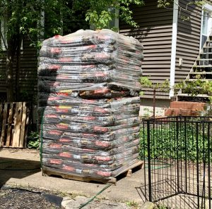 Tall tower of bagged mulch next to a fence and a green house