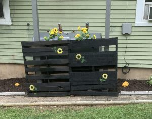 two pallets painted and sunflowers stenciled on them with silk sunflowers in the top of them.