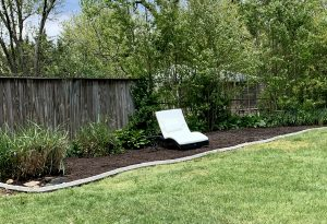 green grass and brown mulch with white lounge chair sitting in the middle
